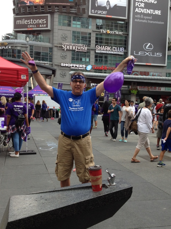 Rob in front of Yonge/Dundas Square holding purple balloons to support Epilepsy Awareness - a cause that is close to his heart